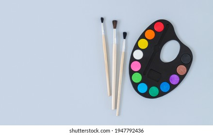 Art palette with paint and brushes top view on gray background, banner with copy space