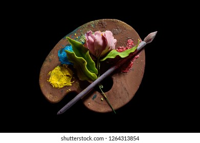 Art palette of sweet cream on a black background.