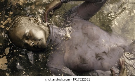 art performance with golden dye, woman with face, hands and hair covered gold is lying in water