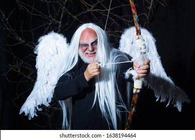 Art photo of a Angelic man. Senior man posing with angel wings. Evil vampire man. Man wizard with fantastic make up on demon face. Druid on black background