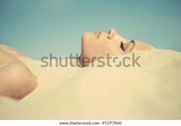 砂に埋もれた美しい女性のアート写真