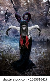 Art photo - a demon faun with bent arms on the banks of a dark river of time.