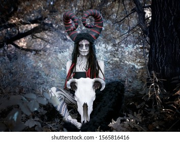 Art photo - demon faun in a fairy forest with a large cow-horned skull between his legs
