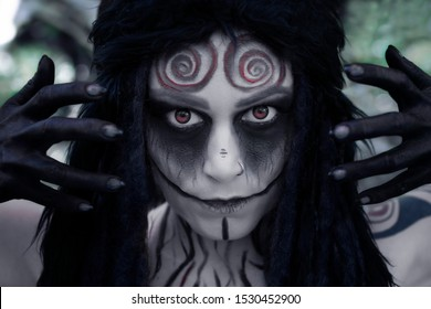 Art photo of a mystic faun with spiral patterns on his forehead and red eyes