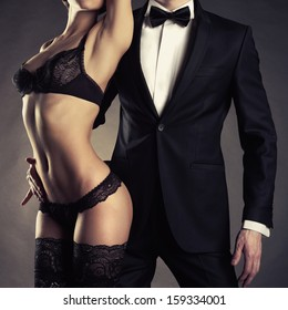 Art photo of a young couple in sensual lingerie and a tuxedo