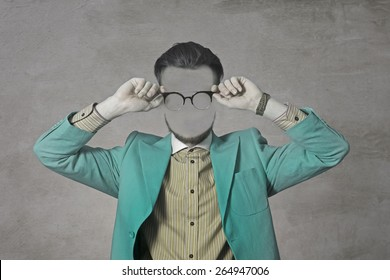Art Photo of a young man without a face. Green suit and glasses. Hipster.