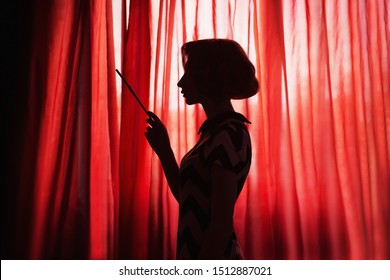 Art photography. Retro silhouette of girl in front of window. Noir photo. Woman smoking a cigarette in mouthpiece. Model with cigarette on red background. Noir silhouette. Theater and film actress
