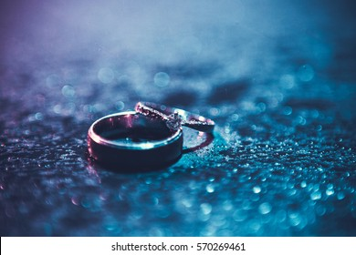 Art picture of wedding rings lying on the wet surface. Blue and violet color light around it.Soft focus on the diamond.