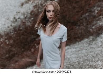 Art portrait of a beautiful fashion girl in the wind on a cloudy day