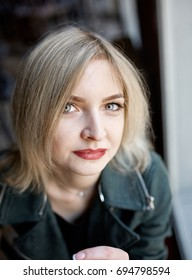 Art portrait of a beautiful girl. gorgeous blond girl in a leather jacket and white dress, having rest in a cafe, green eyes and red lipstick