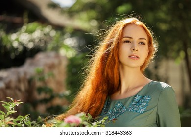 Art portrait of beautiful girl. Pretty woman with long red hair outdoor.