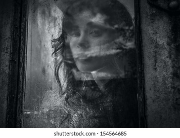 Art portrait of a beautiful young spooky woman, looks through grunge styled rainy window.