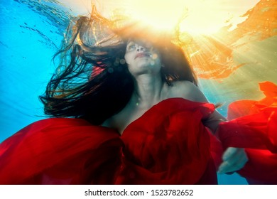 Art portrait of an unusual girl who swims underwater with a red cloth and long flowing hair, against the bright yellow light of the sun from the surface. Close up. Bottom view. Surrealism