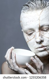 Art portrait of woman covered in clay holding white  cup.  Kintsugi  concept or facial therapy