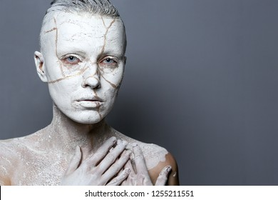 Art portrait woman covered in clay over dark background