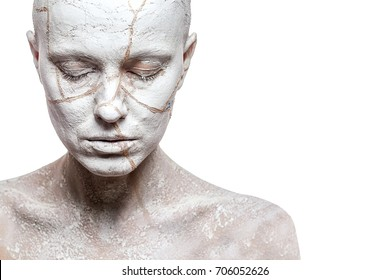 Art portrait of woman covered in clay isolated over white background. Woman face like cracked earth