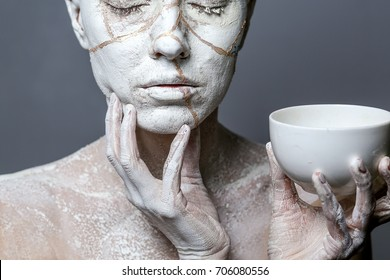 Art portrait of woman covered in clay isolated over grey background. Woman face like cracked pottery holding face and a cup