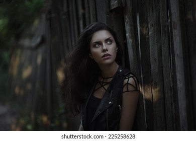 Art portrait of young gorgeous brunette outdoors. Shallow depth of field. Low key
