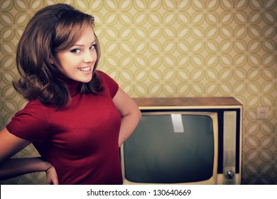 art portrait of young smiling ecstatic woman looking out at camera in room with vintage wallpaper, retro stylization 60-70s, toned