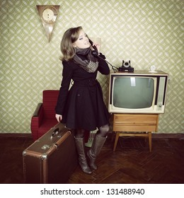art portrait of young woman standing in room calling phone with vintage wallpaper and interior with tv, clocks, chair and suitcase, retro stylization 60-70s, toned