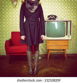 art portrait of young woman standing in room with vintage wallpaper and interior with tv, phone and chair, retro stylization 60-70s, toned
