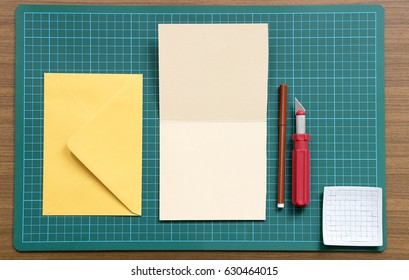 Art Project with color paper blank greeting card on the cutting mate with cutter, felt-tip pen, yellow envelope and decoration material.