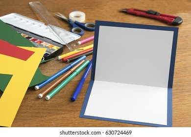Art Project with color paper and blank greeting card on the wooden table