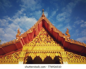 Art in religion on the roof of chapel in Thai temple with clouds and blue sky