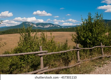 Art rural landscape. Field and grass. Indian summer. Beautiful nature. Sky with mountains in the background. Outdoor recreation