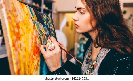 Art school class. Side view of lefthanded female painter creating colorful abstract artwork in studio.