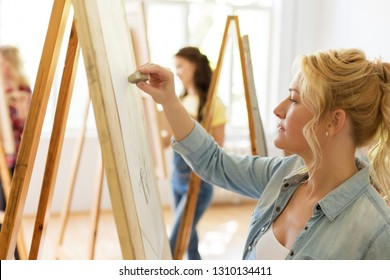 art school, creativity and people concept - woman with eraser and easel drawing at studio