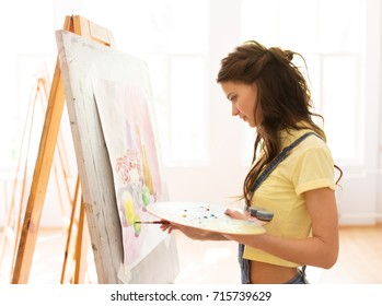 art school, creativity and people concept - student girl or young woman artist with easel, palette and paint brush painting still life picture at studio