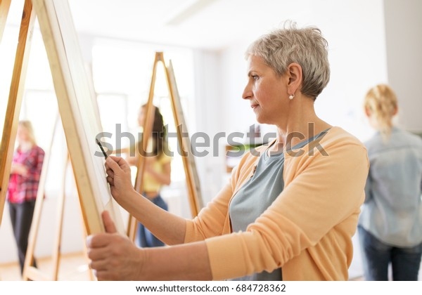 art school, creativity and people concept - happy senior woman artist with easel and pencil drawing picture at studio