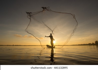 The art of silhouette fishing net in the sunrise background.