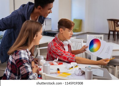 Art students. Promising creative art students feeling curious while looking at color palette choosing suitable color