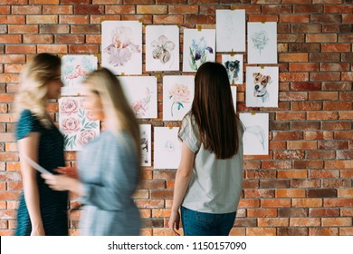 art studio workspace. painter artwork. girl looking at watercolor drawings of flowers and animals on the wall