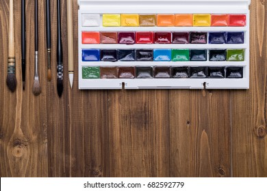 Art supplies (watercolor, palette, brushes) on wooden background with copy space