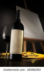 The art of wine depicted with a excellent bottle of wine, a glass and some artist materials, with a blank canvas in the background.