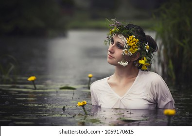 Art Woman with wreath on her head in a swamp in the woods. Wet witch Girl in the lake, mystical mysterious woman bathing outdoors in the swamp. Wreath of wildflowers on her head