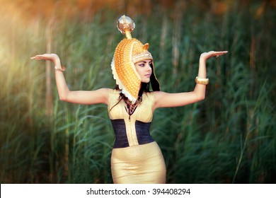 Art work Egyptian Queen Cleopatra. Shooting outdoors in the style of ancient Egypt. A beautiful young girl in gold dress and head wear raising hands in sun light.