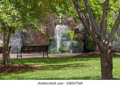 artesian spring in a park surrounded by trees with benches to enjoy the scene
