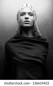 Art-fashion portrait of a glamorous queen-warrior in vintage cape with silver pricks. Black and white (monochrome) studio shot