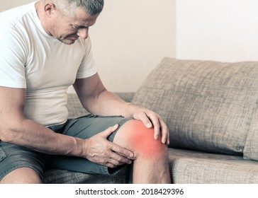 Arthritis is a disease of the joints. A man on a couch, squeezing his knee from excruciating pain