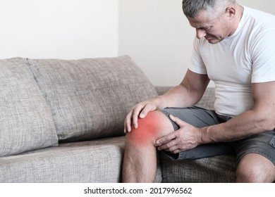 Arthritis is a disease of the joints.A man on a couch, squeezing his knee from excruciating pain
