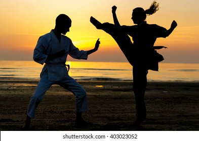 Artial marts fight between master and his pupil at the beach during the sunrise - silhouette - concept about people, lifestyle and sport