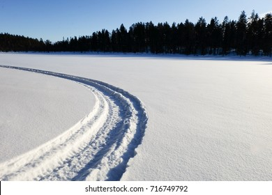 Artic winter in the snow of lapland, track on the frozen lake