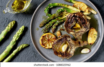 "artichoke and asparagus grill. Tasty vegetables are first cooked for a couple, then fried on a grill, poured with olive oil and spices. spring vegetables.background black slate and plate as ""concrete"""