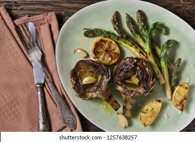 artichoke and asparagus grill. Tasty vegetables are first cooked for a couple, then fried on a grill, poured with olive oil and spices. spring vegetables. Flatlay.