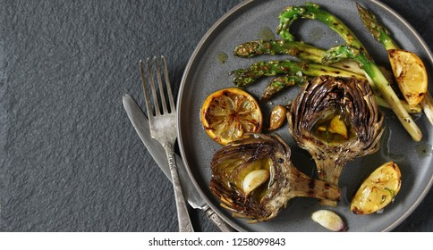 """artichoke and asparagus grill. Tasty vegetables are first cooked for a couple, then fried on a grill. spring vegetables.background black slate and plate as """"concrete"""". Flatlay.  copy space. top view."""
