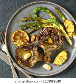 "artichoke and asparagus grill. Tasty vegetables are first cooked for a couple, then fried on a grill. spring vegetables.background black slate and plate as ""concrete"". Flatlay.  copy space. top view."